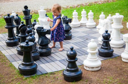 little serious baby girl playing giant chess outside Stok Fotoğraf