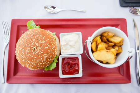 upper view of a burger served with french fries and two sauces