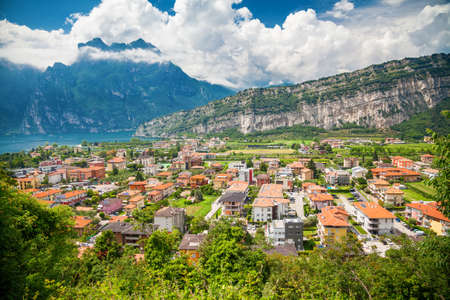 aerial view of the very green small village Torbole with mountains on a background, Lake Garda, Italy