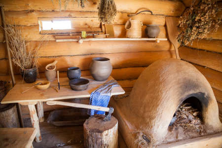 fragment of the interior of the old peasant log cabin - a stove and a table with dish 版權商用圖片