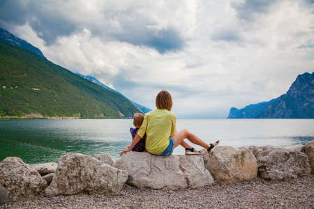 woman and her little daughter relaxing on the beautiful beach of Garda lake, Italy