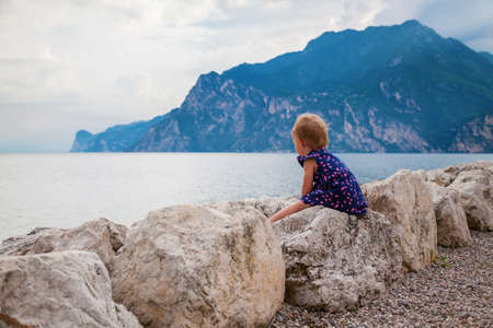 little baby girl sitting on the stones at the edge of Garda lake