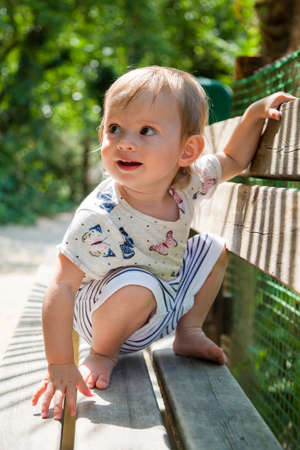 little baby girl sitting on her haunches on a bench