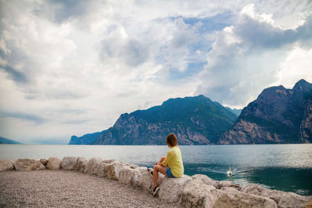 woman sitting on the stones and looking at the Garda lake, Italy