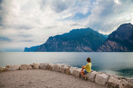 woman sitting on the stones on the beach of Garda lake, Italy