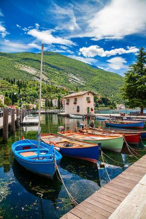 fishing harbor with colorful boats in Nago-Torbole, Garda lake, Trentino-Alto Adige region, Italy Archivio Fotografico