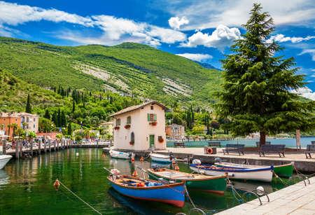 beautiful landscape with boats in the fishing harbor in Nago-Torbole, Garda lake, Trentino region, Italy