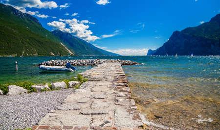 stone pier on a beautiful lake Garda in Torbole, Italy