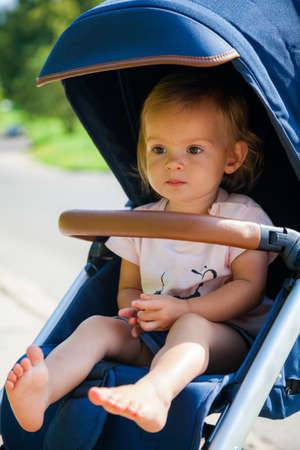 little serious baby girl with bare feet sitting in a stroller