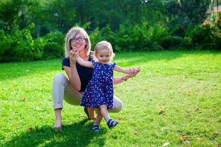 smiling little girl and her mother playing outside in the green park Stock Photo