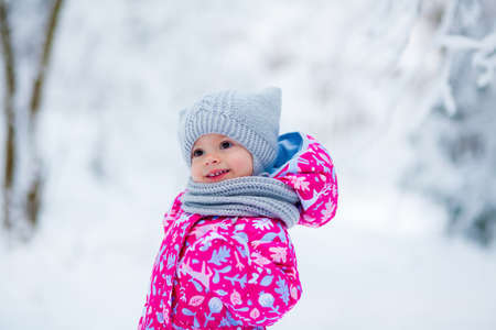 smiling little cute baby girl in winter clothes in a snowy park Stockfoto