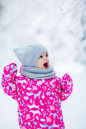 little joyful baby girl with opened mouth in winter park, shes enjoying the snow