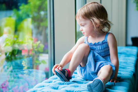 little contemplative girl sitting on a bench sit looking through the window Stockfoto
