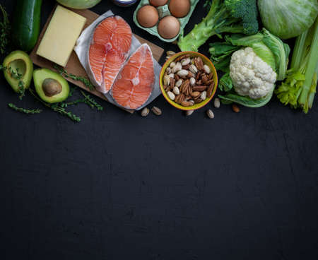 Ketogenic low carbs diet concept. A set of products of the healthy balanced food. Green vegetables, avocado, nuts, salmon, eggs, milk products. Healthy food concept. Black background, top view, copy-space