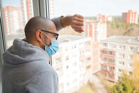 Man in medical mask looking through the window. Isolation at home for self quarantine. Concept home quarantine, prevention COVID-19. Coronavirus outbreak situation Zdjęcie Seryjne