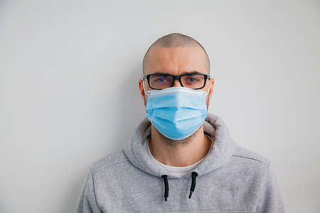 Man in glasses wearing hygienic protective mask to prevent infection such as coronavirus 2019-nCoV, indoor shot Zdjęcie Seryjne