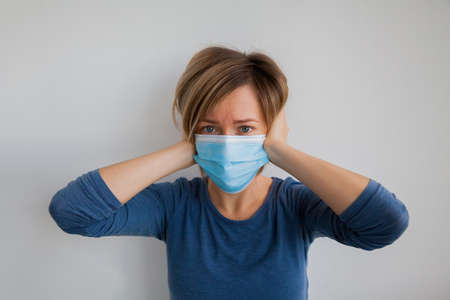 Frightened woman wearing hygienic protective mask to prevent infection such as coronavirus 2019-nCoV. She's in despair, holding her head