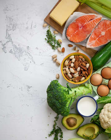 Flexitarian diet. Keto diet. A set of products of the healthy food. Green vegetables, avocado, nuts, salmon, eggs, milk products. Healthy balanced food concept. White background, copy-space, flat lay Imagens