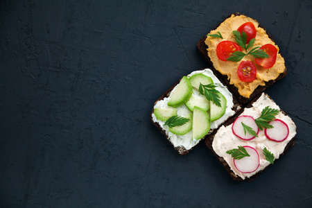 Delicious vegetarian rye bread toasts with cottage cheese, hummus, avocado, raddish and tomato on a black background, copy-space, top view