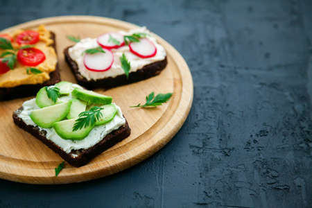 Close-up tasty vegetarian rye bread toasts with cottage cheese, hummus, avocado, raddish and tomato. Wooden board on a black background, copy-space