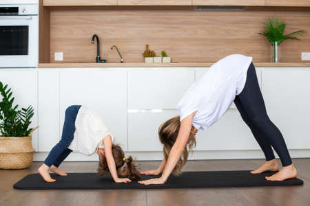 Woman and her little daughter are standing in a downward-facing dog pose while doing yoga together at home Stockfoto