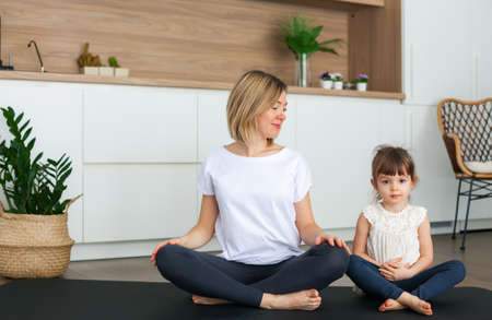 Woman and her cute little daughter are sitting in a lotus position while doing yoga together at home