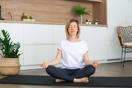 Relaxing woman sitting in a lotus position while doing yoga at home