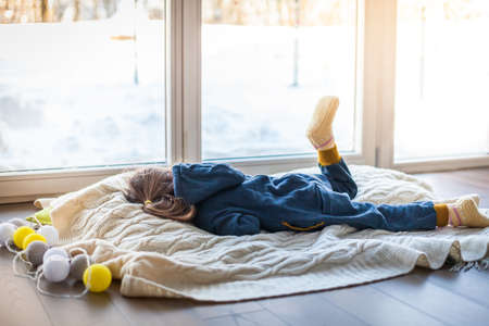 Boring little girl lying on a woolen blanket near the window. it's snowy and cold outside. Stockfoto
