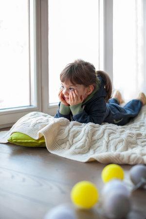 Adorable little girl looking through the window, lying on a woolen blanket. It's snowy winter outside Stockfoto