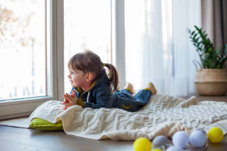 Adorable little girl looking through the window, lying on a woolen blanket. it's snowy and cold outside. Stockfoto