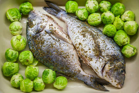 Raw dorado fish with Brussels sprouts for cooking. The concept of a healthy eating.