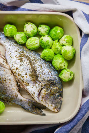 Raw dorado fish with Brussels sprouts in a baking bowl. The concept of a healthy eating. Stockfoto