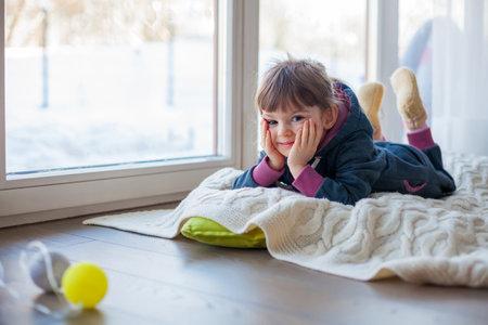 Adorable little girl lying on a woolen blanket near the window, it's snowy winter outside Stockfoto