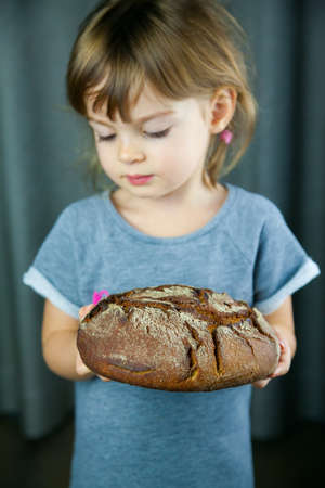 Cute little girl looking at the big circle rye bread in her hands Stockfoto
