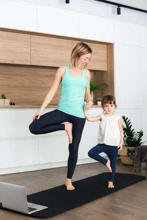 Woman and her little daughter are standing in a Tree Pose while doing yoga together at home