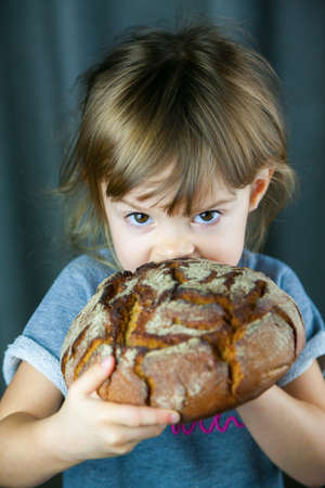 Portrait of a little girl eating a big crunchy circle rye bread, she's very hungry Stockfoto