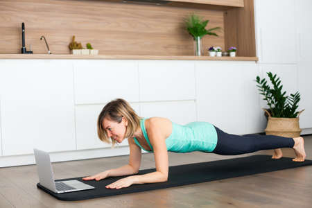 Woman doing a plank exercise while practicing online at home