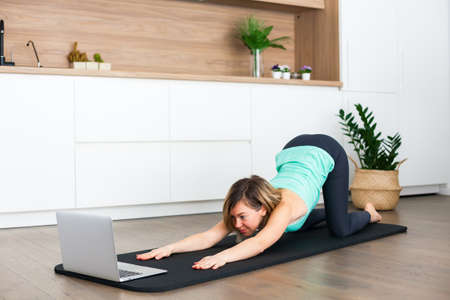 Woman stretching in front of the laptop while doing yoga online at home Stockfoto
