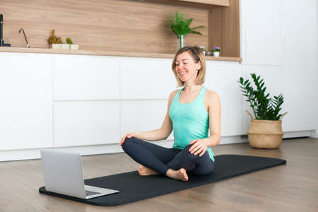 Woman sitting in a lotus position in front of the laptop while doing yoga online at home Stockfoto