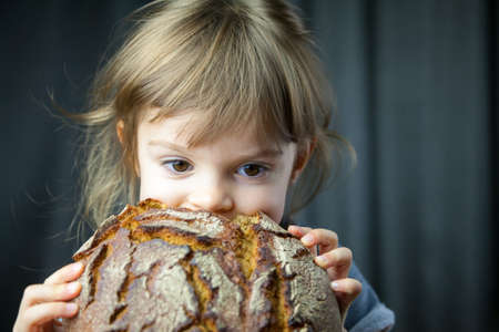 Cute little girl eating a big crunchy circle rye bread, she's very hungry Stockfoto