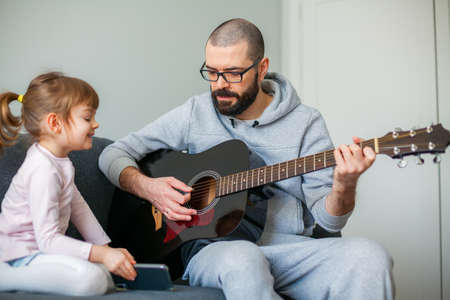 Little girl showing her father a song on a phone while he is playing guitar for her Stockfoto