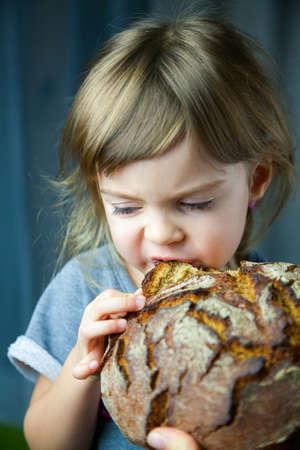 Cute little girl eating a big tasty crunchy circle rye bread, she's very hungry