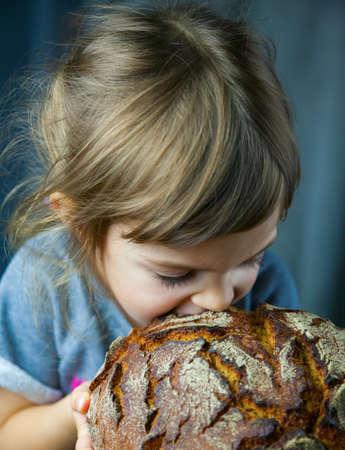 Cute little girl biting a big crunchy circle rye bread Stockfoto