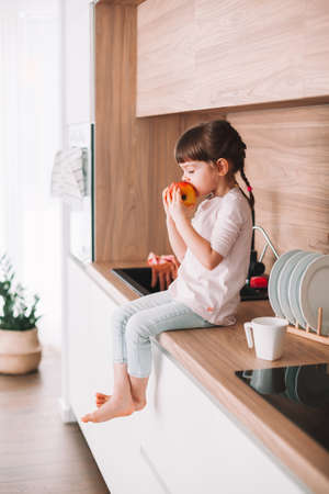 Cute little girl biting juicy red apple sitting on a kitchen surface. Healthy eating concept.