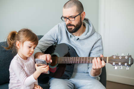 Little girl showing her father a song on a phone. Man is playing guitar for her.