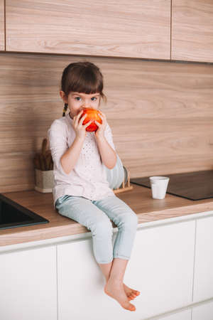 Cute little girl eating juicy red apple sitting on a kitchen surface. Healthy eating concept. Stockfoto