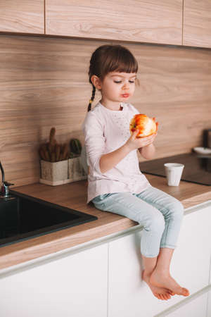 Cute little girl eating tasty red juicy apple sitting on a kitchen surface. Healthy eating concept. Stockfoto