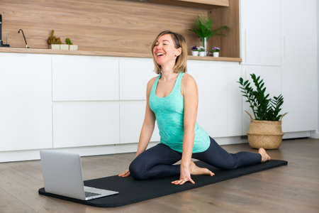 Laughing woman stretching in front of the laptop while doing yoga online at home