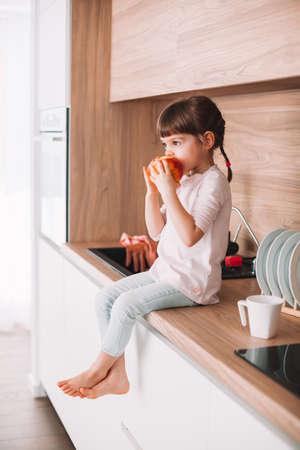 Cute little girl biting red apple sitting on a kitchen surface. Healthy eating concept.