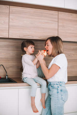 Little daughter sitting on a kitchen surface, giving her mother to try an apple Stockfoto